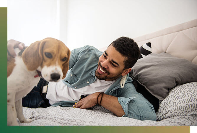 Man playing with small dog on bed